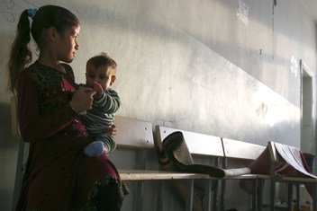 A girl holds a child in the hallway of a school-turned shelter in Tal Abyad of north Ar-Raqqa in Syria, as the conflict enters its 10th year.