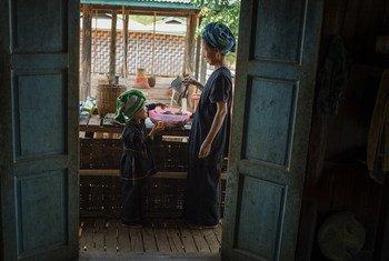 म्याँमार के शन प्रान्त में एक महिला अपने घर पर भोजन पकाने से पहले सब्ज़ियाँ धोते हुए.