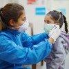 Une infirmière prend la température d'une fille dans un centre de soins de santé primaires à Beyrouth, au Liban, pendant la pandémie de Covid-19.