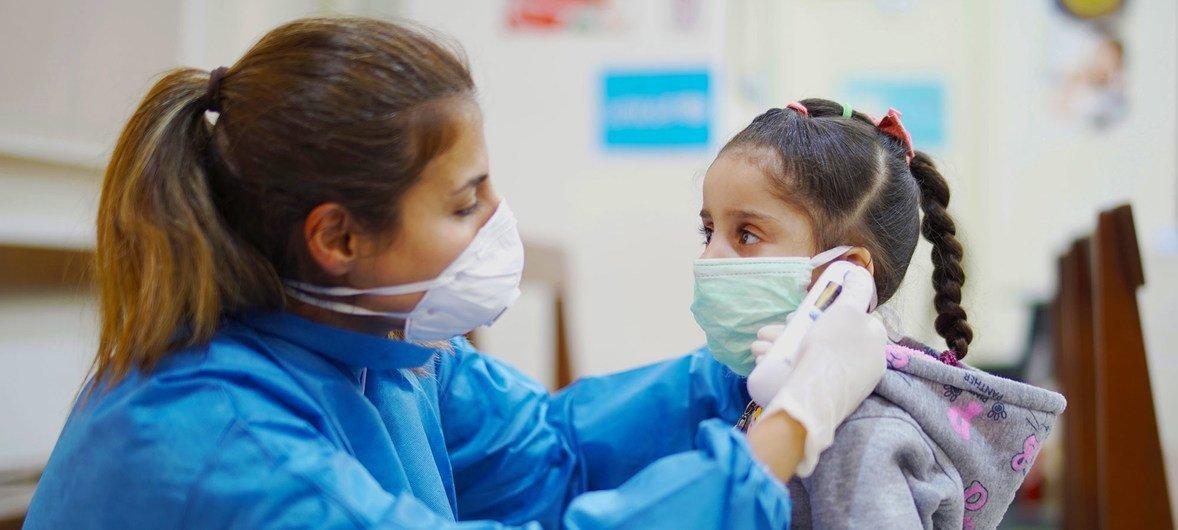 लेबनान के बेरूत के एक स्वास्थ्य केंद्र में एक बच्ची के बुखार को मापा जा रहा है.