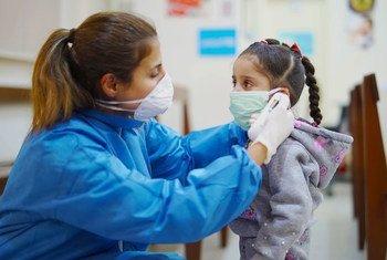 Una enfermera toma la temperatura a una niña en un Centro de Atención Primaria de Salud en Beirut, Líbano, durante el brote de COVID-19.