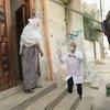 यूएन एजेंसी द्वारा संचालित एक स्वास्थ्य केंद्र से कर्मचारी वृद्ध फ़लस्तीनी महिला को दवाई देते हुए.