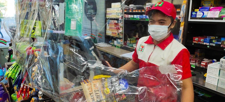 Nas Filipinas, loja de conveniência exige que os funcionários usem máscara, observem a distância física e usem uma barreira de plástico como medida de segurança para evitar a disseminação do Covid-19