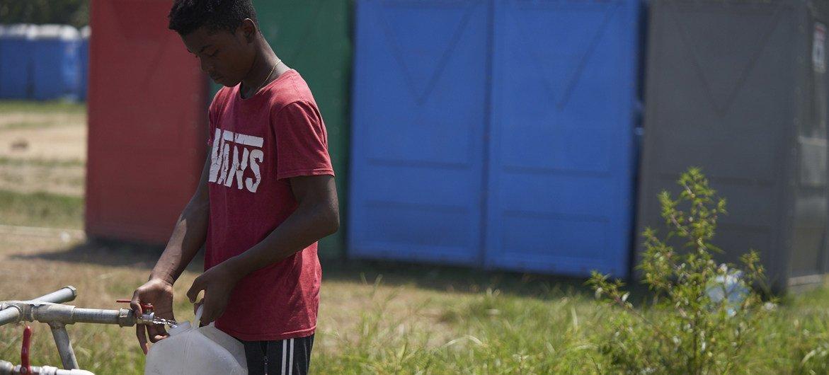 Un adolescente colecta agua potable en una estación migratoria del Darién, en Panamá.