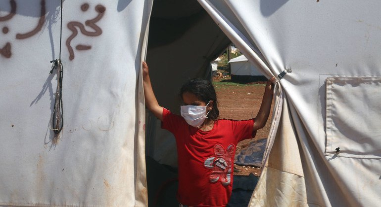 A young girl strands in a tent in a settlement for displaced Syrians in the north of Idlib, in Syria.