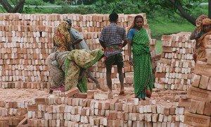 Workers stack bricks at a factory near Dhaka in Bangladesh.