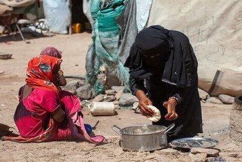 Karima, de 7 años, ve cómo su madre prepara pan en Yemen, donde el conflicto ha agravado la fatla de alimentos.