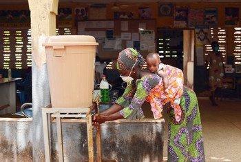أم تغسل يديها في مرفق لغسل اليدين في عيادة مجتمعية في تامالي، بغانا.