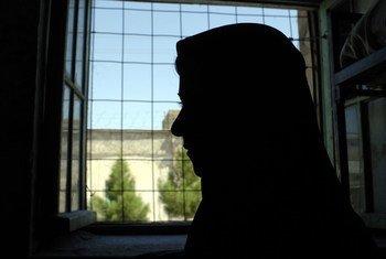 अफ़ग़ानिस्तान के हेरात में एक महिला क़ैदी खिड़की के पास खड़ी है.