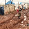 A girl walks through the mud carrying her younger brother at the Khair Al-Sham IDP camp in Idlib Governorate, Syria.