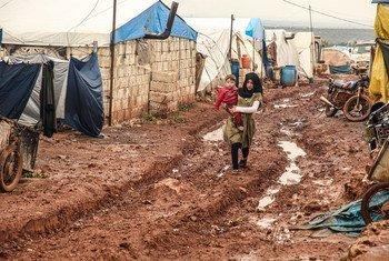 فتاة تسير في وحل وهي تحمل أخاها الصغير في مخيم خير الشام في محافظة إدلب السورية.