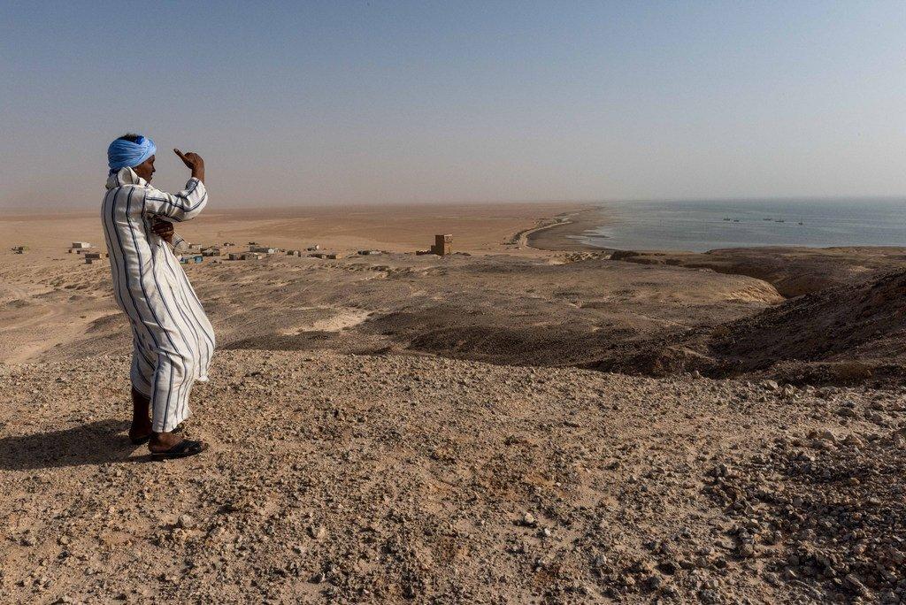 Un homme regarde l'Atlantique depuis les cotes de la Mauritanie, pays du Sahel, situé au sud du désert du Sahara
