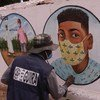 Artist in the Central African Republic, CAR, painting on walls various tips on how to protect oneself from COVID-19.