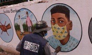 فنان في جمهورية إفريقيا الوسطى يرسم على الجدران نصائح مختلفة حول كيفية الحماية من كوفيد-19.