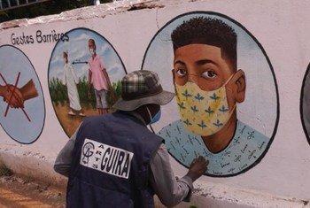 मध्य अफ़्रीकी गणराज्य में एक कलाकार दीवारों पर कोविड-19 के ऐहतियाती उपायों पर चित्रकारी कर रहा है.