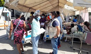 2021年8月14日,海地发生7.2级地震一天后,粮食计划署海地主任皮埃尔·霍诺特(右)在海地耶雷米的圣安托万医院与一名工作人员交谈。