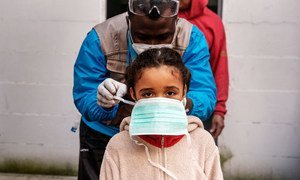 A seven-year-old girl is given a protective mask prior to a health screening in the informal settlement in Rome, Italy, where she lives.