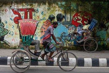 Katikati ya siku yenye jotot katli mwendesha baisekli akipumzika kando ya barabara Dhaka nchini Bangladesh.