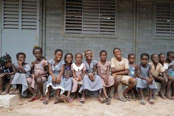Des enfants assis devant leur nouvelle école faite de briques en plastique recyclé à Sakassou, dans le centre de la Côte d'Ivoire.
