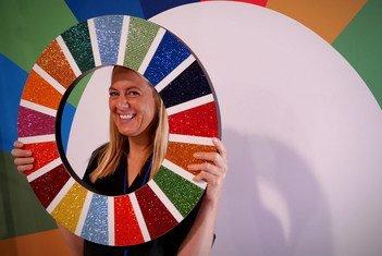 今年9月联合国大会第74届会议高级别会议期间,一名与会者手持2030年可持续发展议程图标留影。