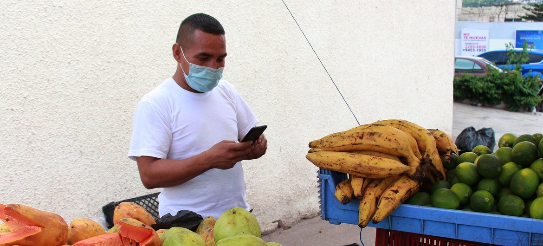 Hombre vendiendo en su puesto de verduras en Tegucigalpa, Honduras.