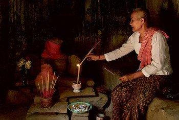 一位比丘尼在柬埔寨吴哥窟的一处遗迹内诵经祷告。