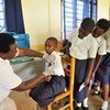 فتاة صغيرة في رواندا تتلقى مصلا في حين تنتظر زميلاتها في المدرسة دورهن بقلق.
