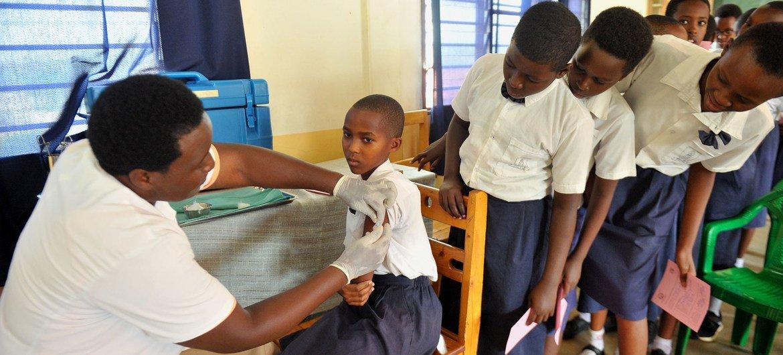 Una joven de Rwanda recibe su vacuna contra el Virus del Papiloma Humano mientras sus compañeros de clase miran atentamente.