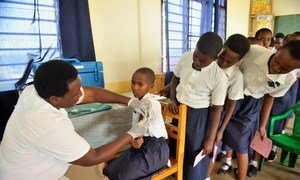A young girl in Rwanda receives her HPV vaccination while her classmates nervously wait their turn.