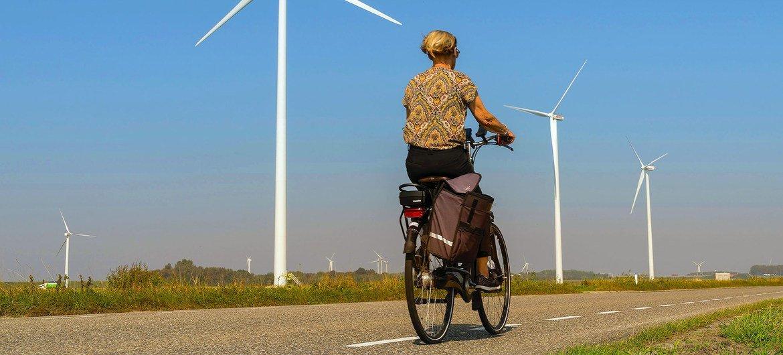 नैदरलैण्ड्स के ग्रामीण इलाक़े में एक महिला, पवन चक्कियों के पास से होकर गुज़र रही है.