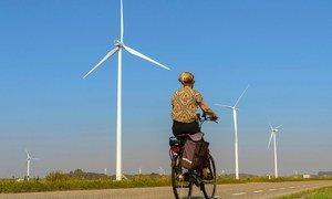 Une femme passe devant des éoliennes sur une route de campagne à Heijningen, aux Pays-Bas.