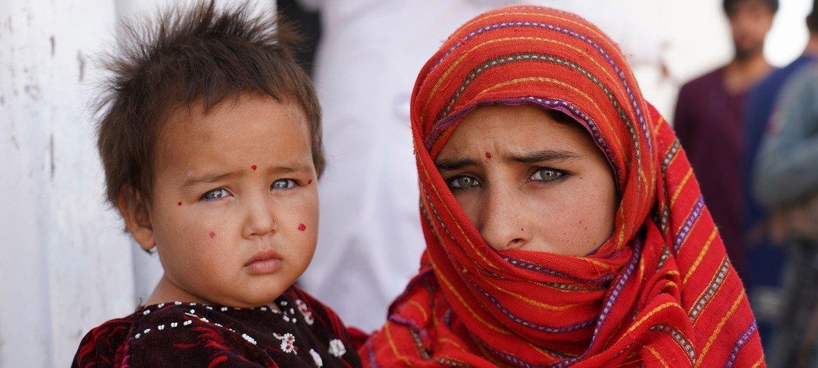 Menina de 12 anos segura a irmã em campo para deslocados internos em Herat, no Afeganistão