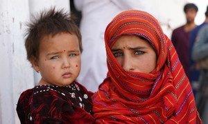 Una niña de doce años junto a su hermanita bebé afuera de un campamento de desplazados internos en Afganistán