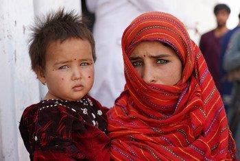 Une fillette de 12 ans tient sa petite sœur dans ses bras devant un centre de nutrition dans un camp pour personnes déplacées près de la ville occidentale de Herat. Les deux filles sont venues ici avec leur famille pour échapper aux combats dans leur province.