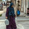 Une mère transporte de l'eau fournie par l'UNICEF dans un camp de fortune en Syrie.
