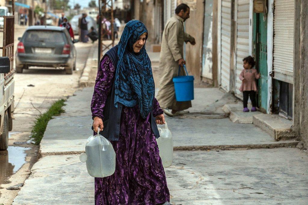 儿童基金会每天一直用卡车将水运送到叙利亚临时营地的家庭。一名母亲提着刚刚取回的水。