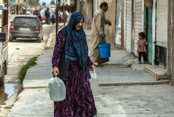 यूनीसेफ़, सीरिया में, अस्थाई शिविरों तक ट्रकों के ज़रिये पानी पहुँचाने में मदद करता रहा है. ऐसे ही एक ट्रक से पानी लाते हुए एक महिला.
