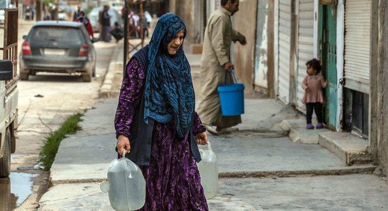 أم تحمل قناني مياه توزعها اليونيسف بالشاحنات يوميا إلى العائلات في المخيمات المؤقتة في الجمهورية العربية السورية.