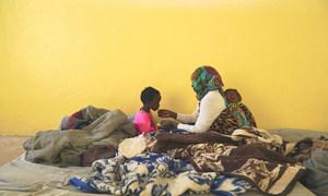 利比亚班加西的一处监禁中心内,一位母亲正在喂孩子吃饭。