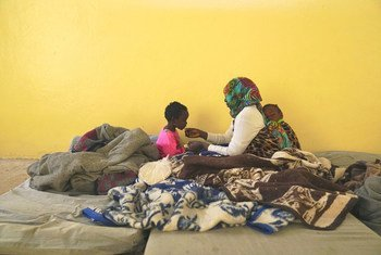 A detainee mother, with sleeping baby on her back, feeds her other child some bread inside the female room of a detention centre in Benghazi, Libya.