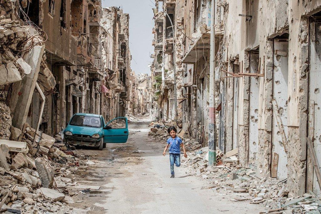 Un enfant traverse les débris et les destructions du centre-ville de Benghazi, en Libye (photo d'archives)..