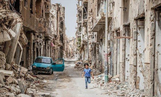 Criança corre entre destruíção em Benghazi, na Líbia