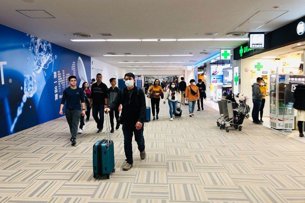 Des voyageurs portant des masques à l'aéroport international de Narita, à Tokyo, au Japon.