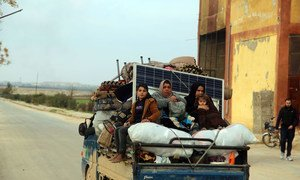 Women and children ride in the back of a truck as families flee from Saraqeb and Ariha in Syria's south rural Idlib Governate to escape escalated conflict.