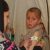 A health worker screens a four-year-old boy for malnutrition at an IDP camp in north-east Syria.