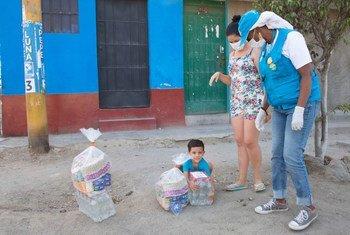 Un niño y su madre, ambos venezolanos, reciben ayuda de las agencias de la ONU en un barrio de Lima.