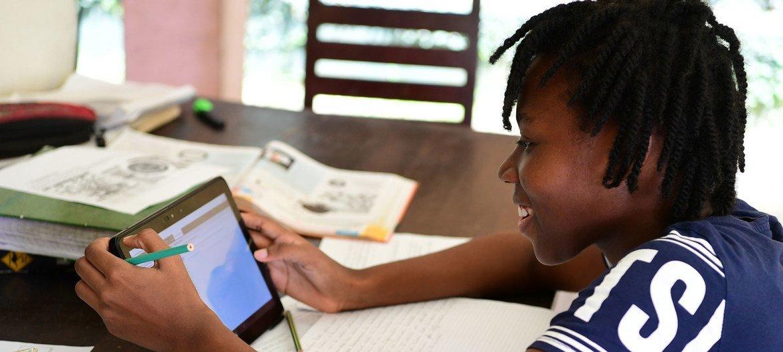 Une jeune fille étudie en ligne chez elle à Abidjan, en Côte d'Ivoire.