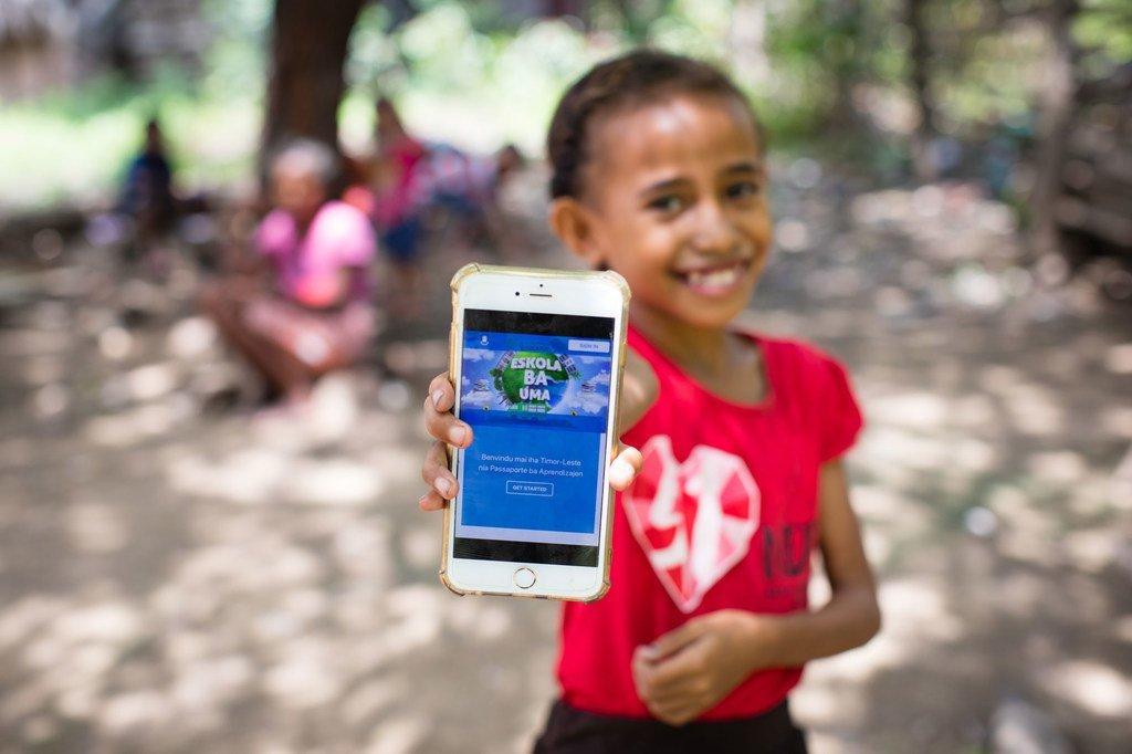 Msichana mdogo huko Timor-Leste akionesha jukwaa lake la mtandaoni ambalo atatumia kudsoma wakati shule zimefungwa kutokana na janga na COVID-19