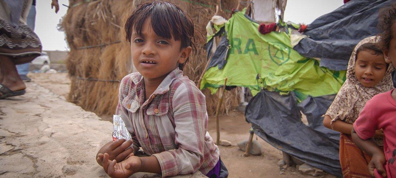 طفل يلهو في وقت تقف والدته في طابور للحصول على الماء في مخيم للنازحين في عدن جنوبي اليمن.