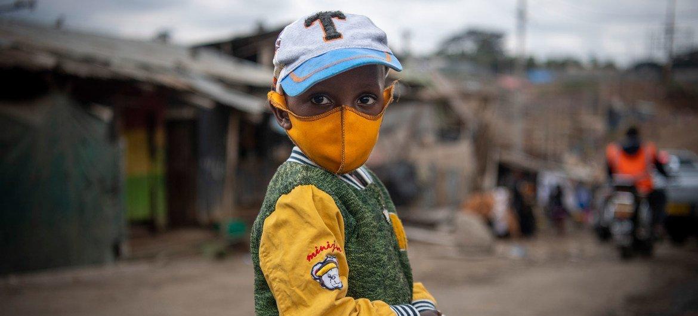 A young boy wears a face mask as he walks through Mathare, an informal settlement in Nairobi, Kenya.